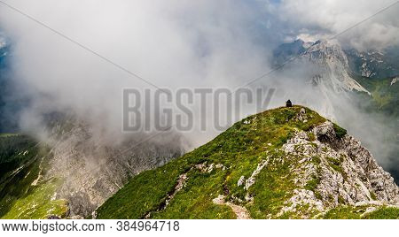 Young Woman From Behind Summerhiker With Backpack Resting On Hill Onsteep Slopes, Panoramic Peaks