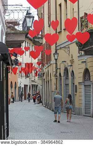 Arona, Italy - August 25, 2020: People In The Streets Of The Old Town Under Heart Shaped Symbols