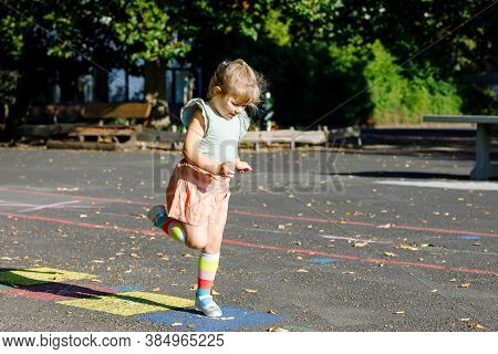 Cute Little Toddler Girl Playing Hopscotch Game Drawn With Colorful Chalks On Asphalt. Little Active