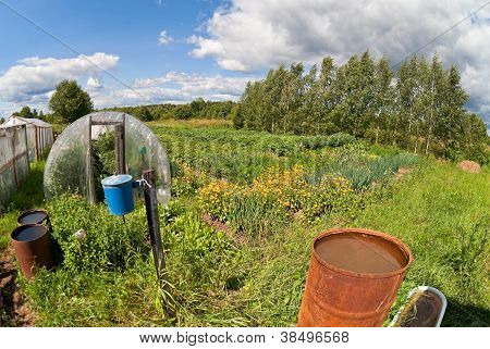 Countryside Landscape With Retro Washstand And Rusty Water Barrels
