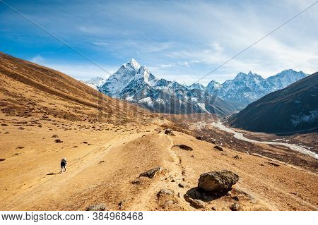 Young Woman Trekking In Valley Dukh Koshi River Leading To The Everest Base Camp With Ama Dablam Pea