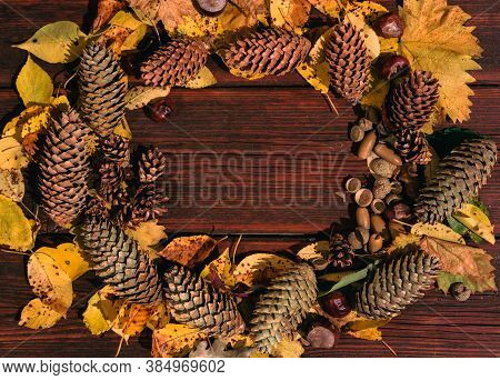 A Lot Of Yellow Fallen Leaves On The Wooden Table, Acorns And Pine Cones Nearby. The Autumn Atmosphe