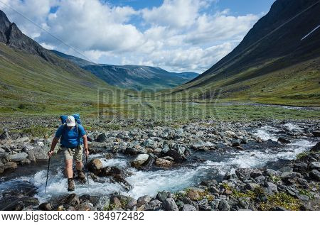 Hiking in Swedish Lapland. Man trekking alone crossing river in northern Sweden. Arctic nature of Scandinavia in summer day
