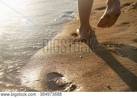 A Strip Of Surf And Waves On A Beach With Golden Sand. Salt Sea Water On The Sand. A Child Runs Alon