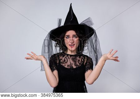 Halloween Concept - Portrait Of Young Surprised Woman In Black Witch Halloween Costume And Hat Over