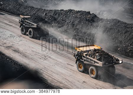Open Pit Mine Industry. Yellow Mining Truck For Coal Moves Along Dusty Quarry Road