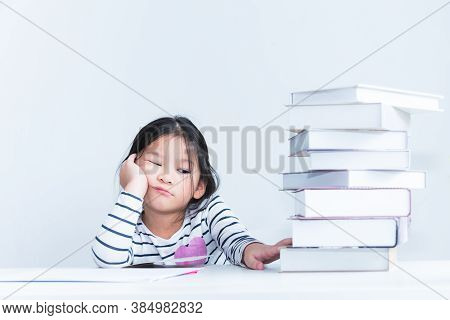 A 6 Year Old Asian Girl, Looking At The Stack Of Books Stacked On White Table With Boredom, On White