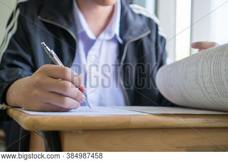 Asian Students Holding Pencil In Hand Doing Multiple-choice Quizzes Or Testing Exams Answer Sheets E