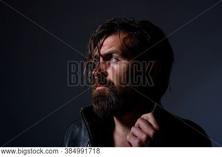 Brutal Bearded Biker. Handsome Man In Leather Jacket Looks Into The Distance While Holding The Edge