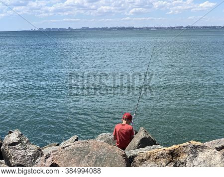A Boy With A Fishing Rod At The Sea Is Fishing. Fishing For Children On The Seashore With A Spinning
