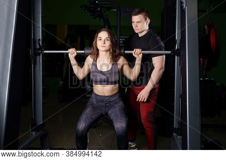 Lesson with a trainer in the gym. The trainer helps the woman to perform the exercise on the Schmitt simulator.