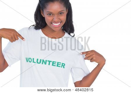Smiling young woman wearing volunteer tshirt and pointing to it on white background