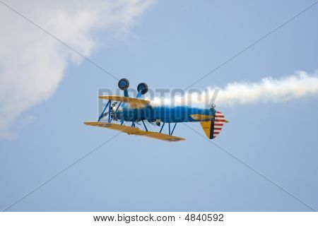 A Pre Wwii Trainer Does A Roll And Trails Smoke As He Flies Past The Crowd