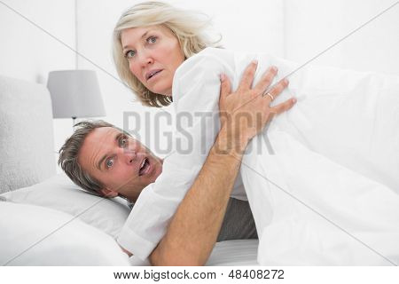 Shocked couple caught in the act at home in bed