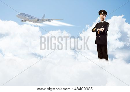 pilot is in the form of arms folded, against the sky, the clouds and the plane poster