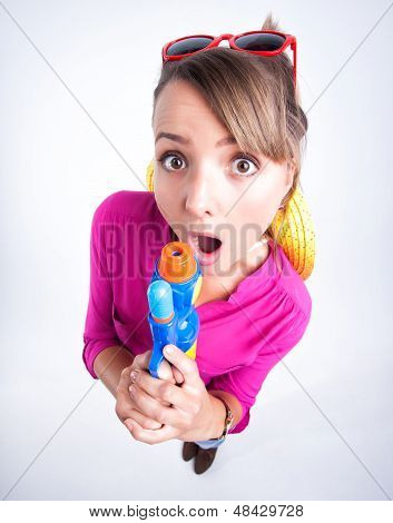 Cute Girl Looking Surprised Holding A Water Gun In The Studio