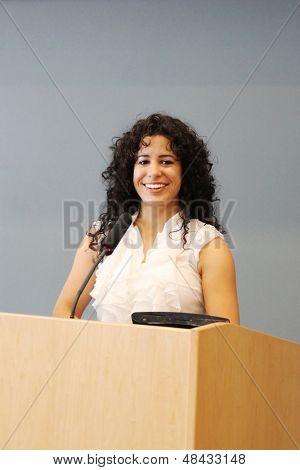 Woman behind a podium, ready for a speech