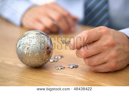 Businessman solving globe puzzle concept for business solutions and strategy