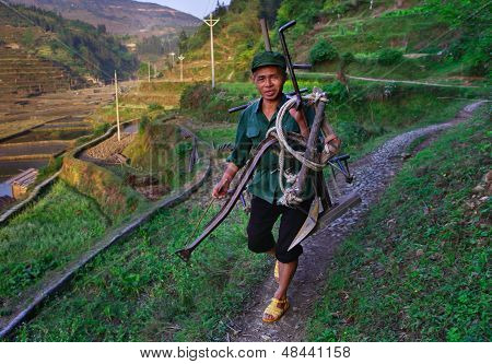 Chinese Peasant Cultivates Rice Field Hoe. Man Carries Plow The Rice Field