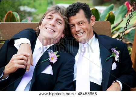 Handsome gay couple relaxing on a swing at their wedding reception.