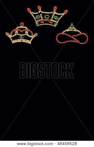 Three Kings Crowns against black background.