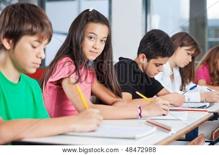 Portrait of teenage girl sitting with classmates writing at desk in classroom