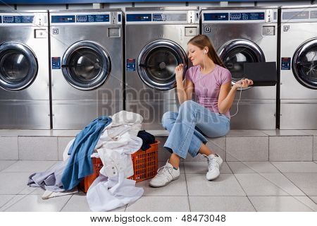 Young woman with laundry basket enjoying music while sitting at laundromat