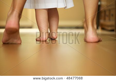 Portrait Of A Mother Teaching Baby To Walk Indoors