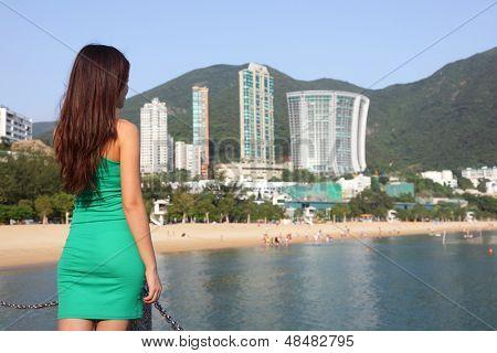 Hong Kong tourist woman at Repulse Bay beach. Beautiful Asian woman in summer dress enjoying view. Hong Kong travel and tourism concept.