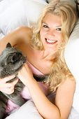 portrait of a beautiful happy girl at home in bed with her cat poster