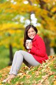 Happy woman drinking coffee in fall forest / city park outdoor. Girl sitting relaxing enjoying hot drink, coffee or tea in disposable cup outside in beautiful fall foliage. Asian Caucasian female, 20s poster