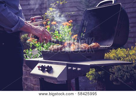 Man Cooking Meat On Barbecue