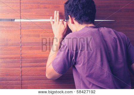 Young Man Peeping Out Through Venetian Blinds