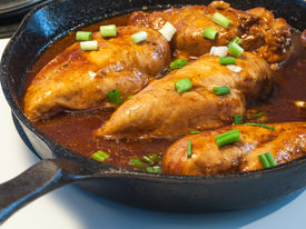 Chicken Breasts Cooking In A Cast Iron Pan With Green Onions