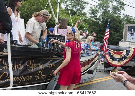 Man shucks oysters on a float in the Wellfleet 4th of July Parade in Wellfleet, Massachusetts.