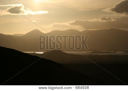 The Sun approaches the Luss Hills at it moves towards setting over Loch Lomond poster