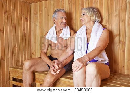 Two happy seniors holding their hands in a sauna in a hotel
