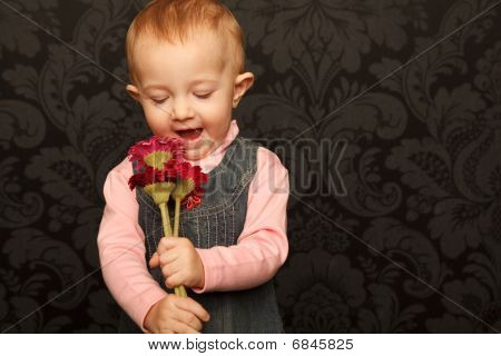 Portrait of little girl with flowers in her hands against ornamental wall