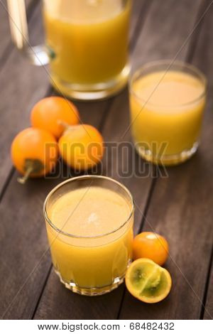 Freshly prepared juice out of Naranjilla or Lulo fruits (lat. Solanum quitoense) with fruits on the side and in the back (Selective Focus Focus on the front rim of the glass) poster