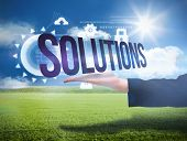 Businesswomans hand presenting the word solutions against sunny green landscape poster