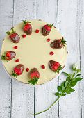 Homemade strawberry cake with flower on wooden board poster