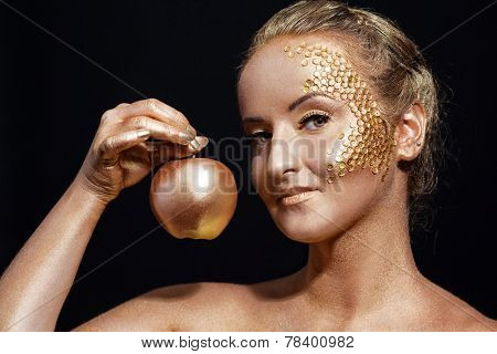 girl with golden bodyart posing with golden apple in her hands on black background