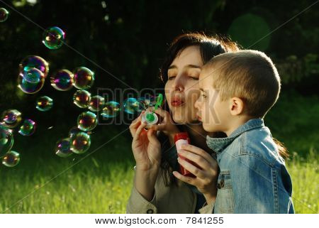 Mother And Son Making Soap Bubbles Outdoors