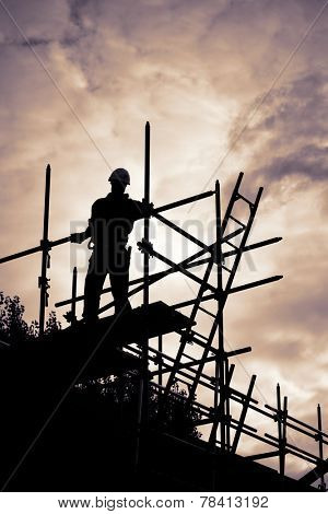 silhouette of construction worker with ladder on scaffolding. Purple toned