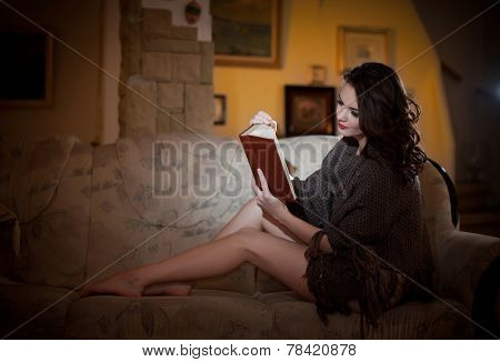 Beautiful young woman sitting on sofa holding a book, vintage scenery. Attractive brunette girl