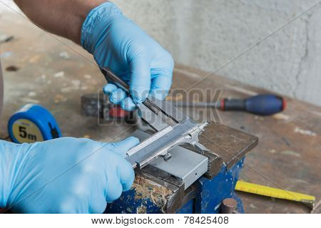 A Mechanic With Blue Gloves And A Vernier Caliper