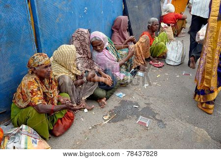 Indian woman begars on a busy road