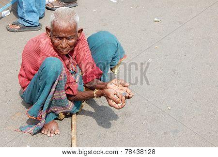 Poor Indian woman seeking help on a busy road