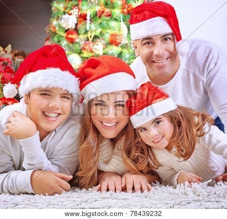 Portrait of happy family in Christmas eve at home, cheerful parents with two cute kids lying down on the floor near beautiful decorated Xmas tree
