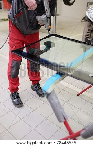 working to apply the adhesive sealant on the windshield
